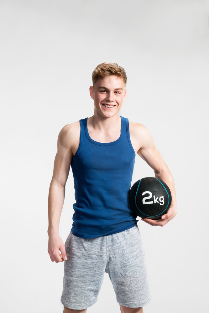 3158e531f3f07 Handsome hipster fitness man in blue tank top shirt and gray shorts holding  medicine ball.