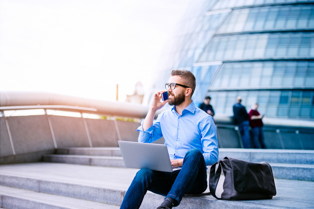 Handsome hipster manager sitting on stairs on sunny day, working on laptop, talking on a smart phone, London, City Hall