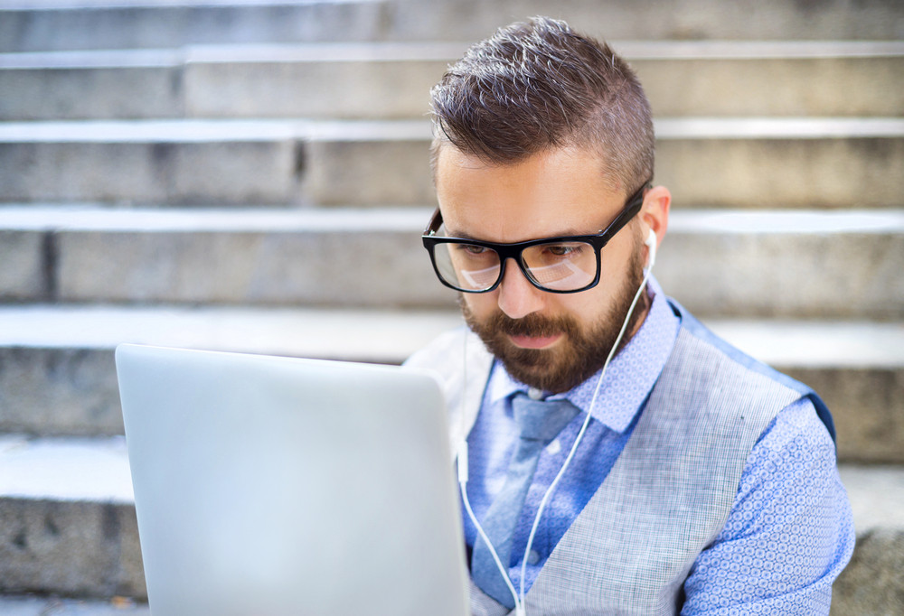Handsome hipster modern businessman using laptop in the city