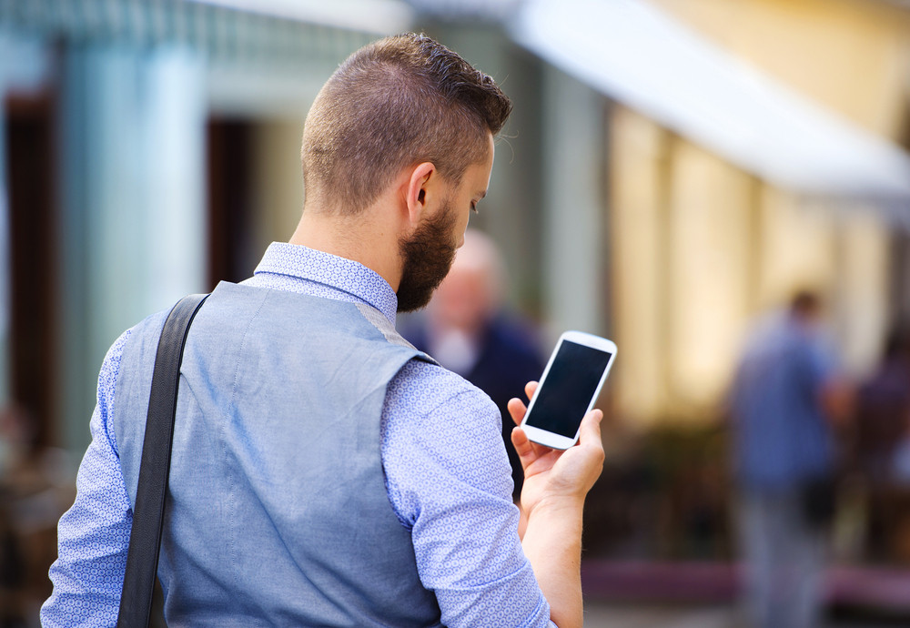 Handsome hipster modern businessman with beard walking in town with mobile phone