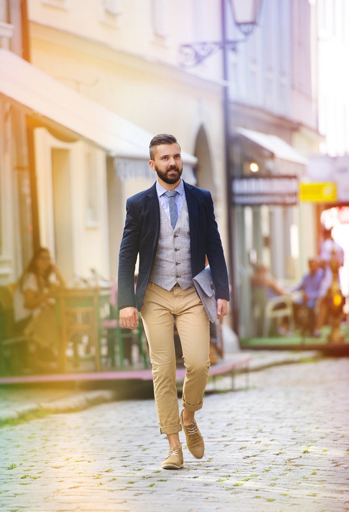 Handsome hipster modern businessman with briefcase walking in town