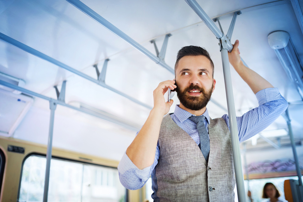 Handsome hipster modern man calling by mobile phone in tram