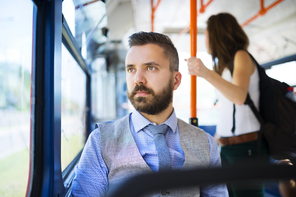 Handsome hipster modern man traveling by tram in town