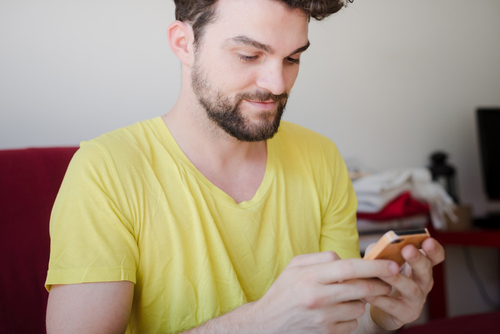 handsome hipster modern man using cellphone at home