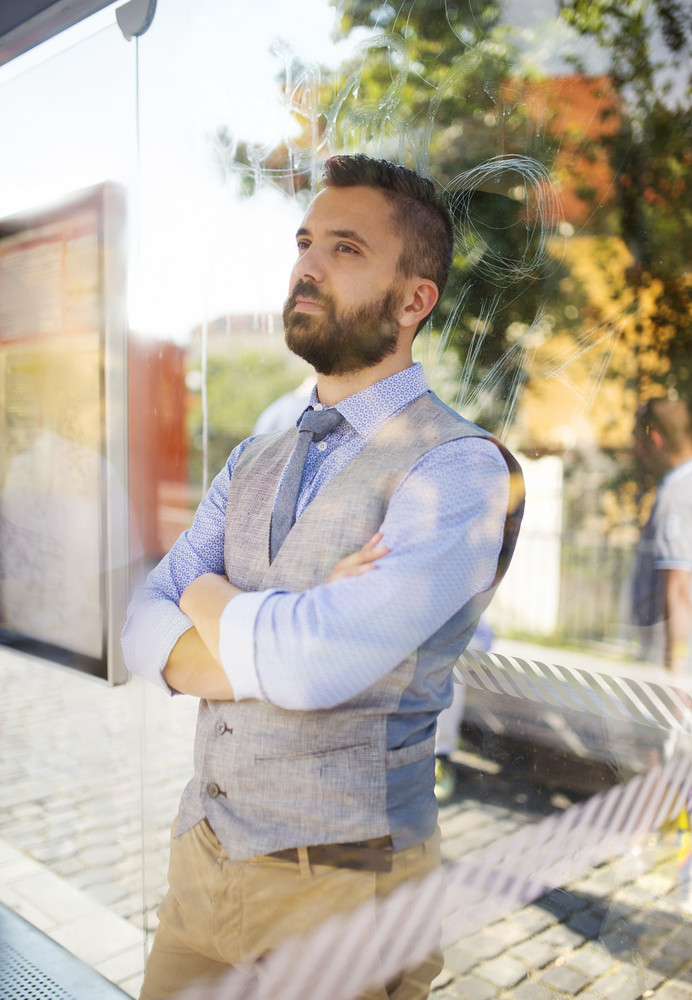 Handsome hipster modern man waiting for bus on bus stop