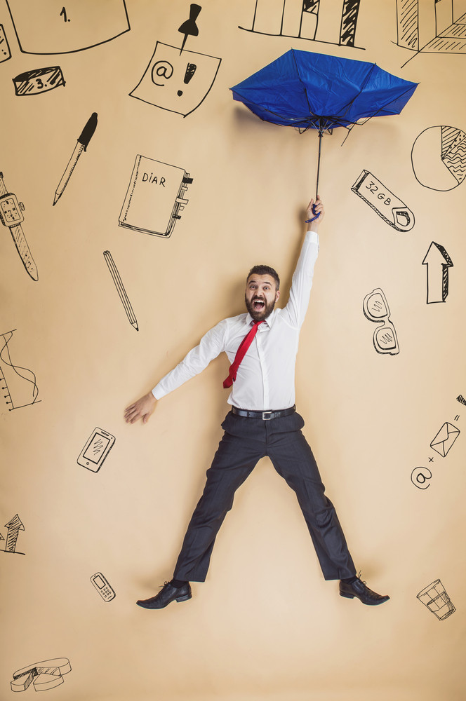 Handsome manager with umbrella falling down. Studio shot on beige background.