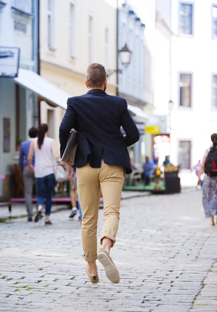 Handsome modern hipster businessman with briefcase hurrying to work