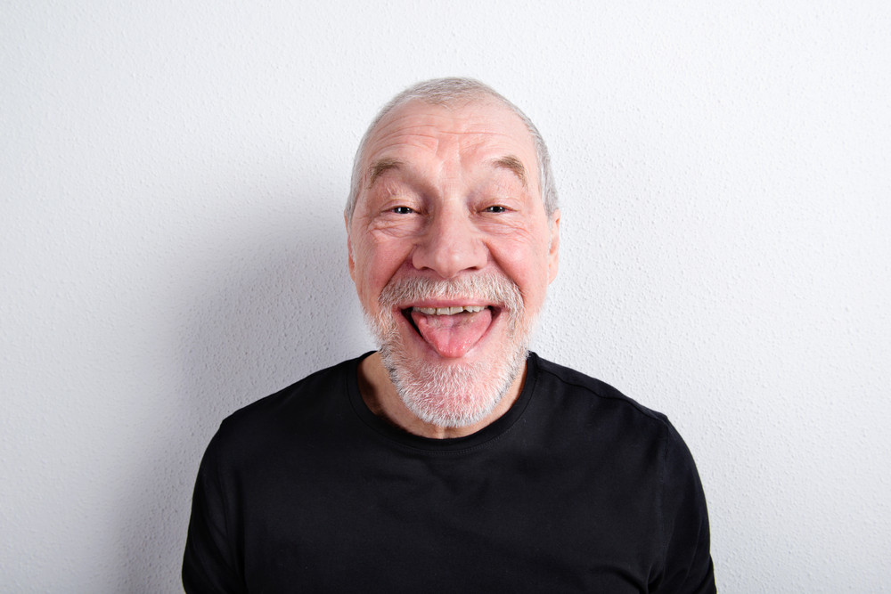 Handsome senior man in black t-shirt, making funny face, sticking tongue out
