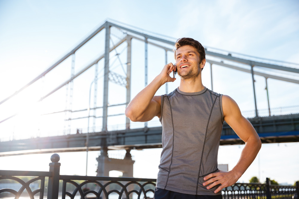 Handsome smiling young man in sports uniform is talking on the mobile phone while standing at the bridge