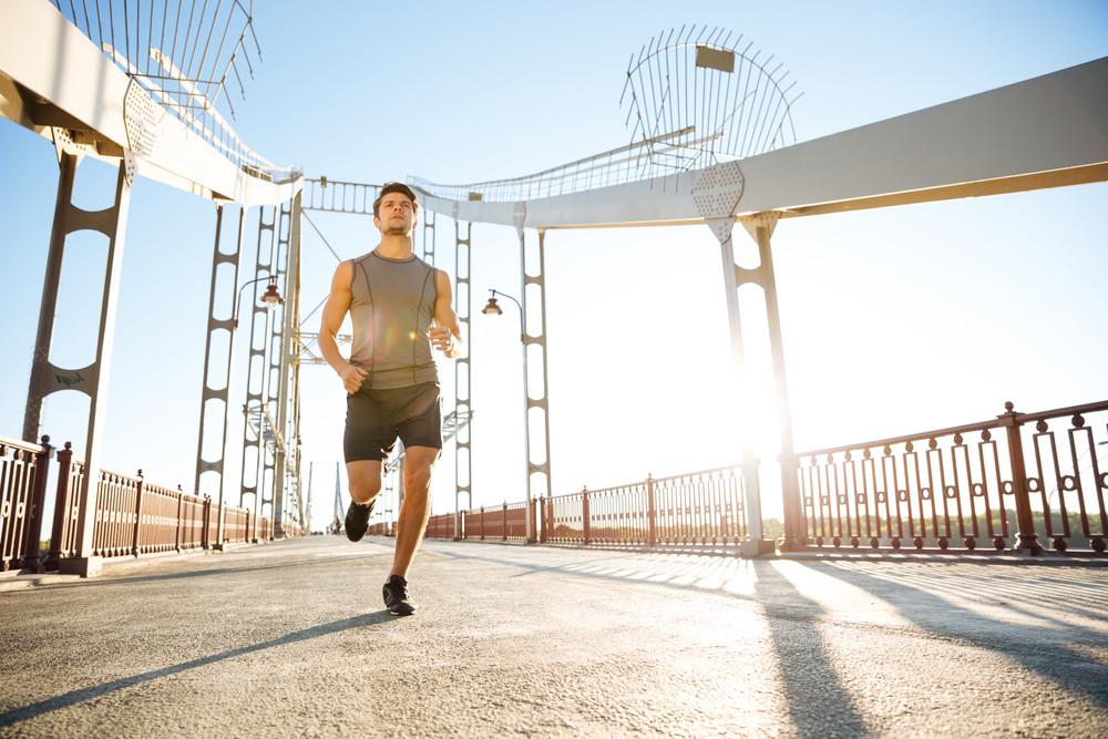 Handsome sports man running fast along big modern bridge at sunset light