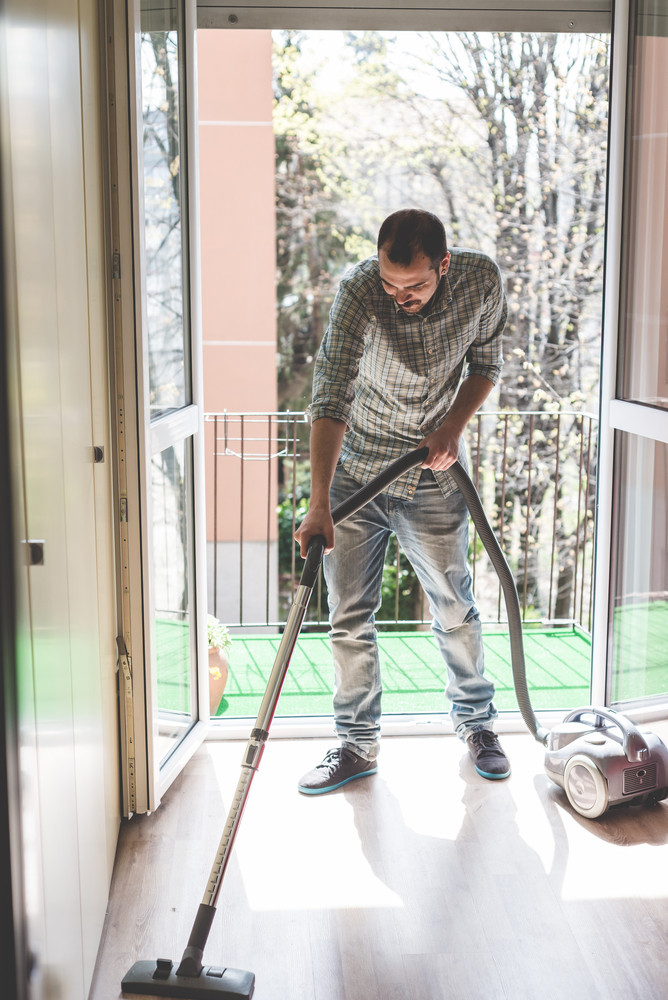 handsome stylish man using hoover at home