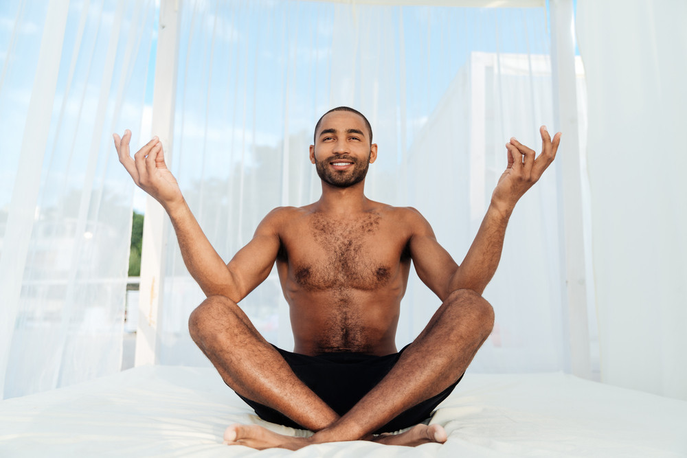 Handsome young african man in shorts sitting and meditating on the beach bed