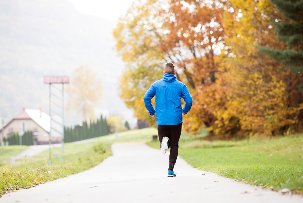 Handsome young athlete in blue jacket running outside in colorful sunny autumn nature on an asphalt path leading through green grass. Trail runner training for cross country running.