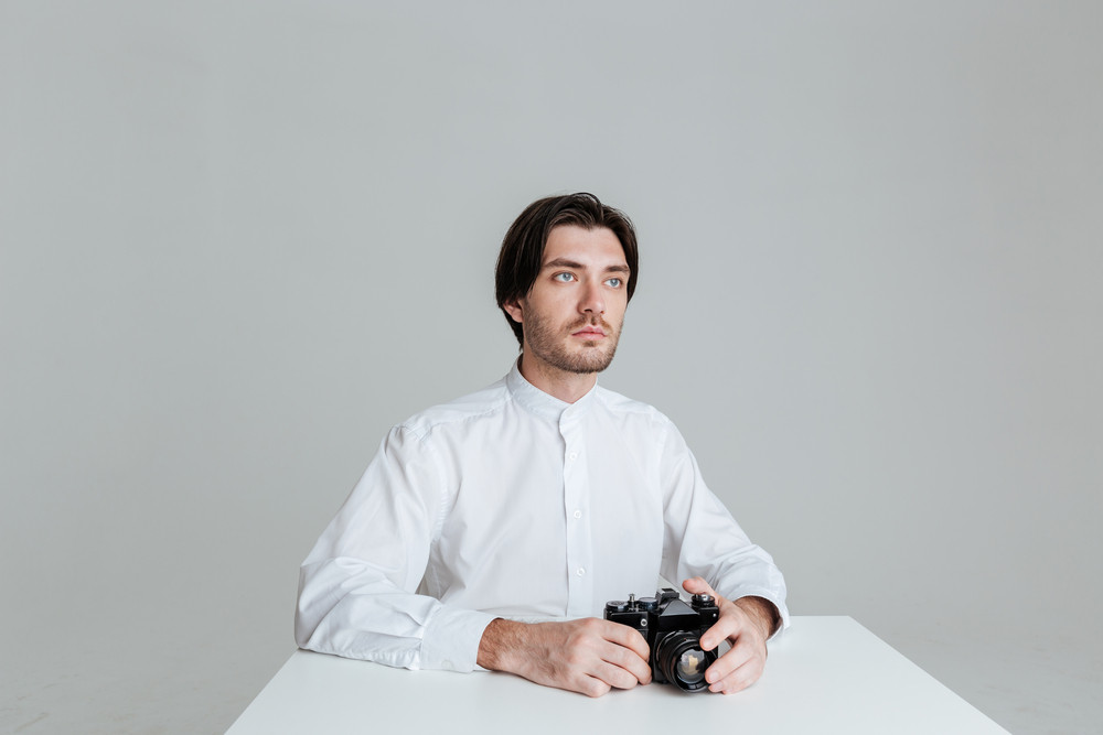 Handsome young brunette man sitting at the table holding camera isolated on the gray background
