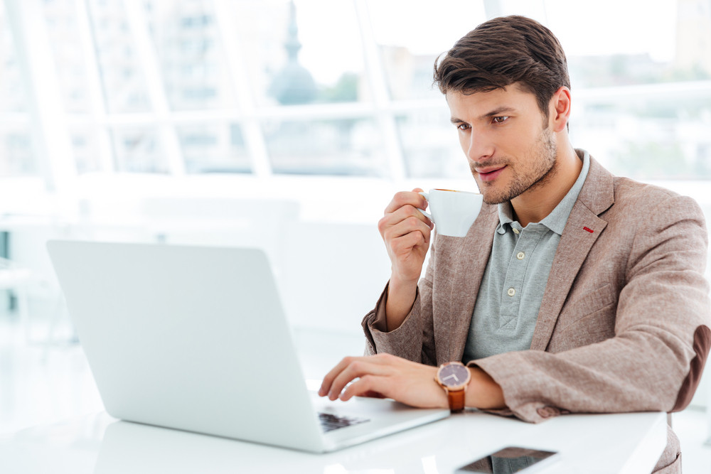 Handsome young businessman having cup of coffee and using laptop indoors