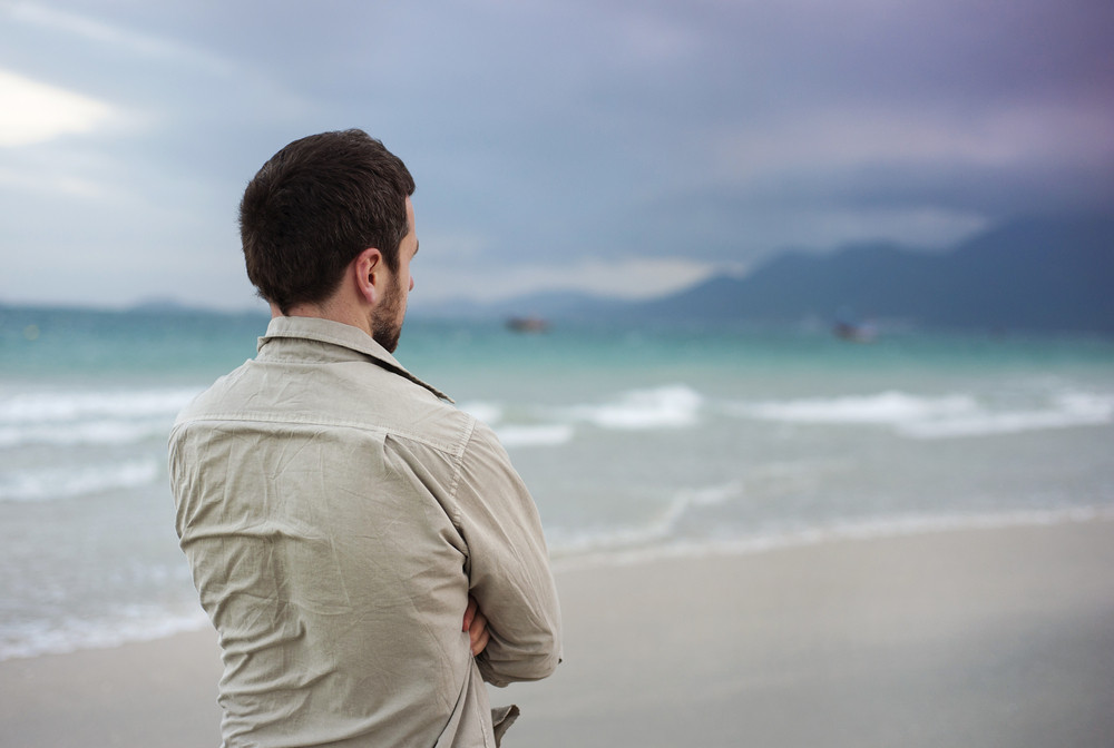 Handsome young Caucasian man walking alone on the beach