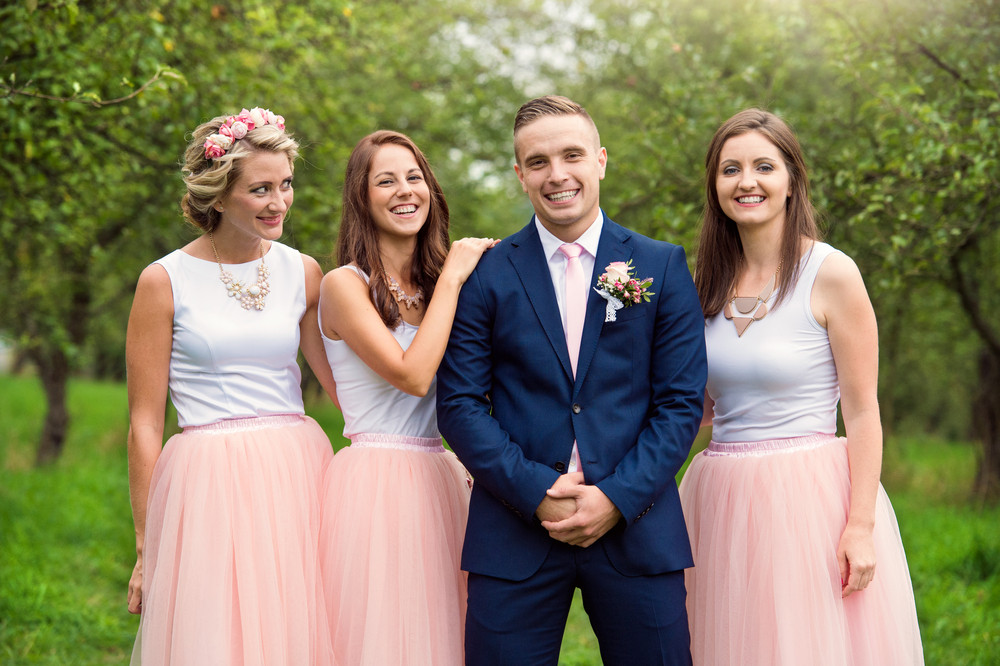 Handsome young groom with her bridesmaids outside in nature