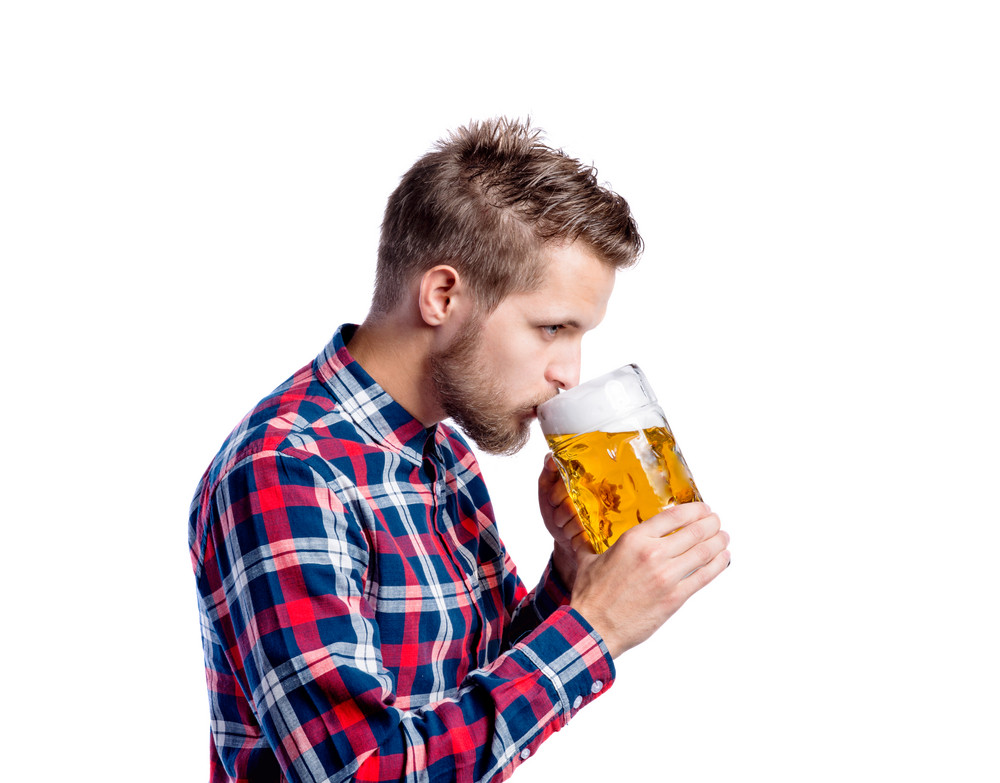 Handsome young hipster man in checked shirt holding a mug of beer, drinking from it. Oktoberfest. Studio shot on white background, isolated.