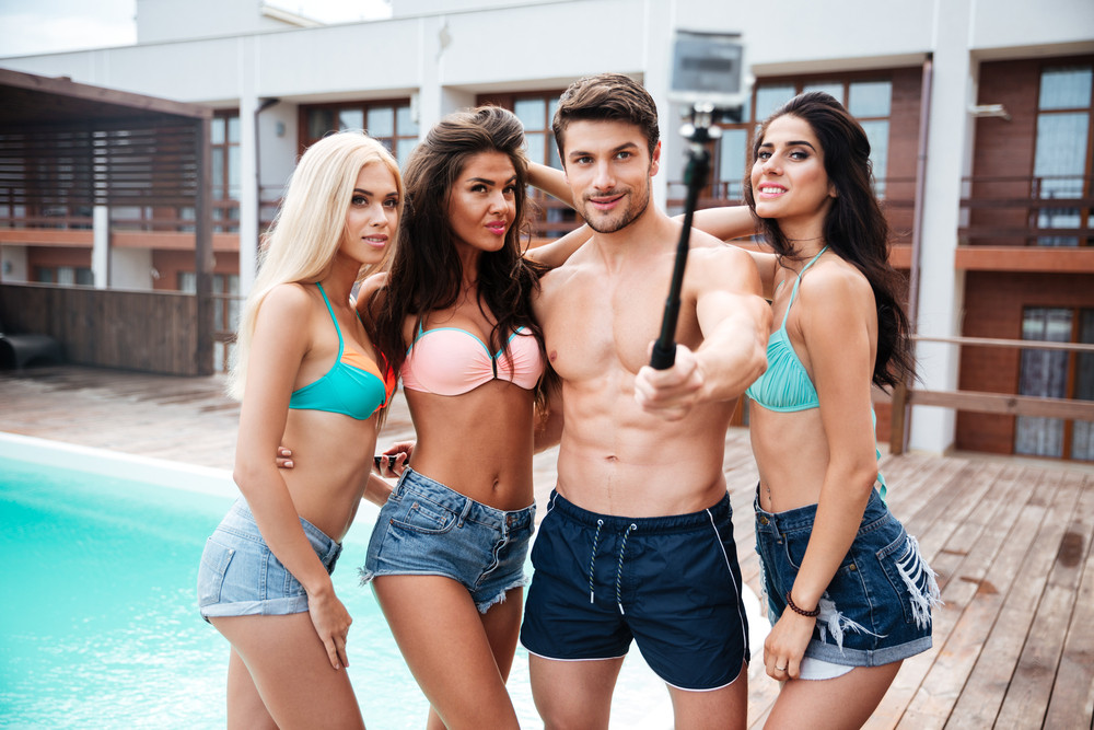 af0f498166852 Handsome young man and three girls taking selfie with smartphone and selfie  stick standing near swimming