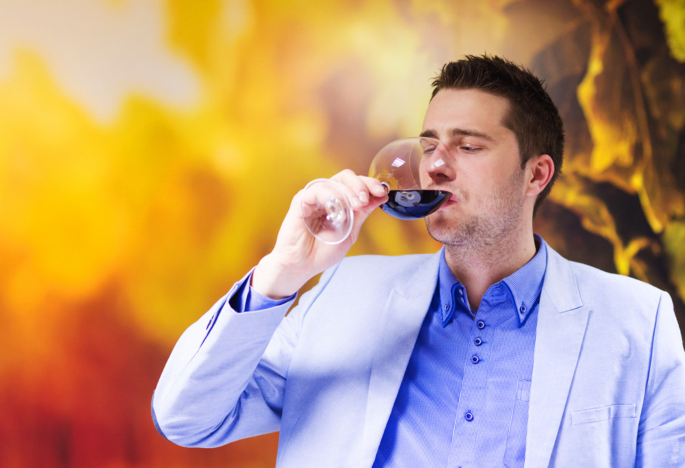 Handsome young man enjoying a drink in a wine bar