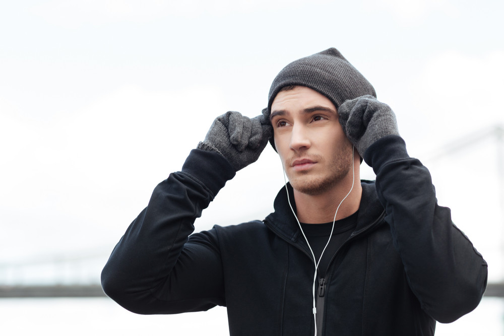 Handsome young man in hat and gloves standing and listening to music with earphonrs outdoors