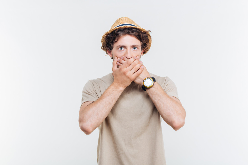 Handsome young man in hat coveres his mouth by hands over white background