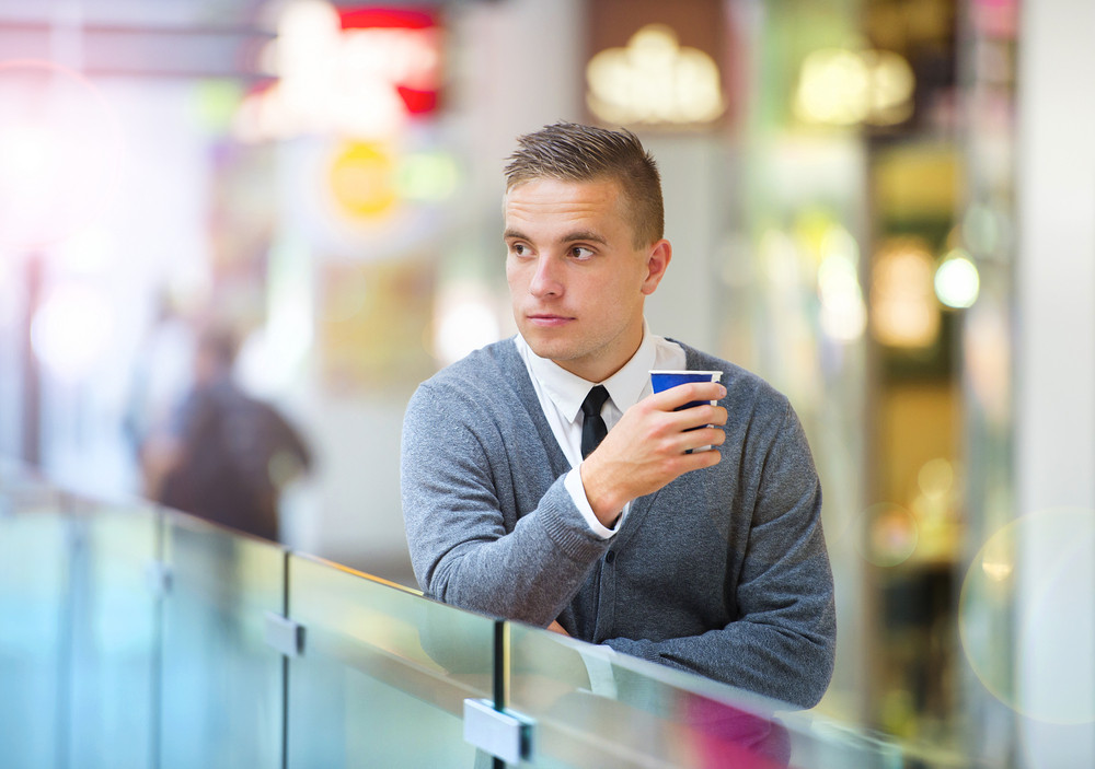 Handsome young man in shopping mall drinking coffee
