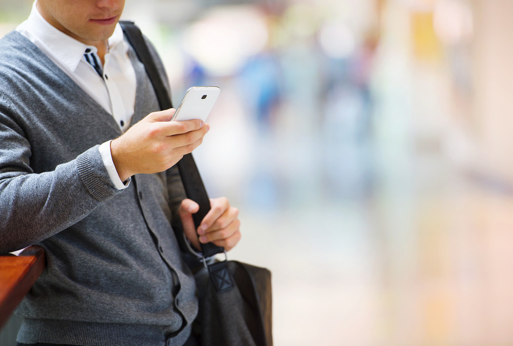 Handsome young man in shopping mall using mobile phone