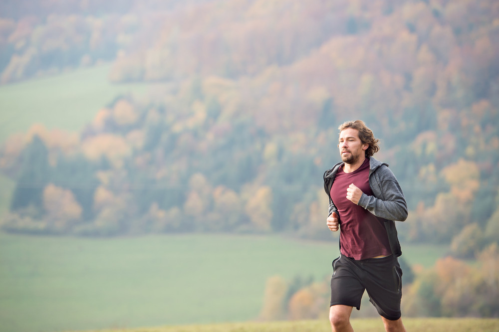 Handsome young man running in colorful sunny autumn nature.