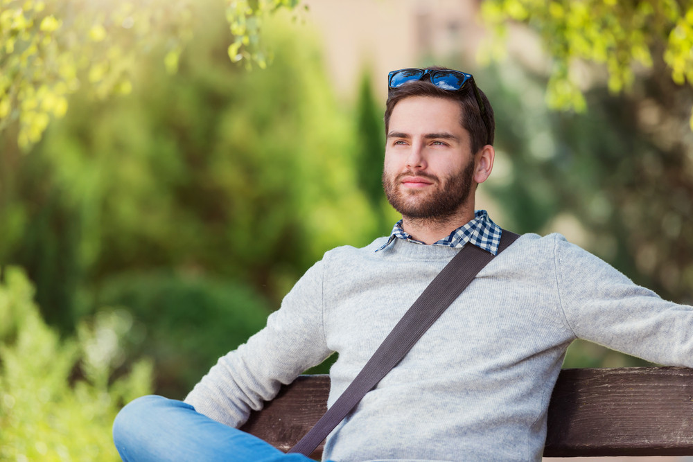 Handsome young man sitting on park bench