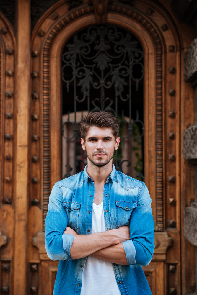Handsome young man standing in front of the beautiful wooden door waiting for someone outdoors