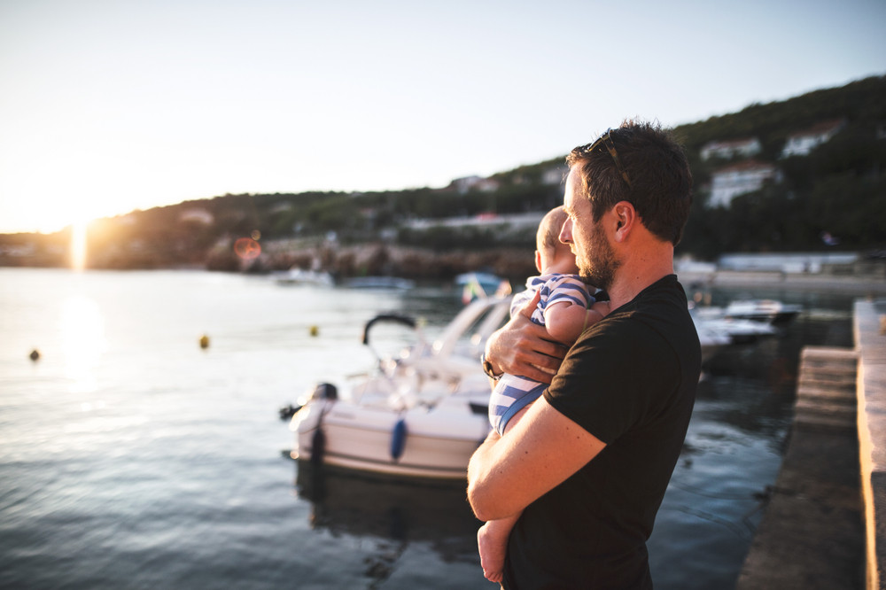 Handsome young man standing on wooden pier holding his baby son in his arms enjoying their time at seaside.