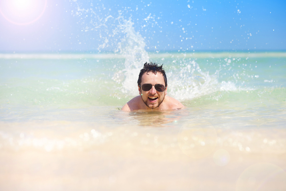 Handsome young man swimming in the sea at paradise beach in Phu quoc island, south of vietnam