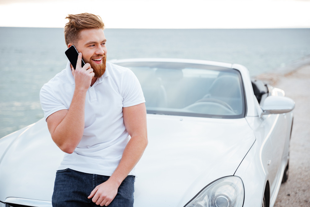 Handsome young man talking on the mobile phone while leaning at his car