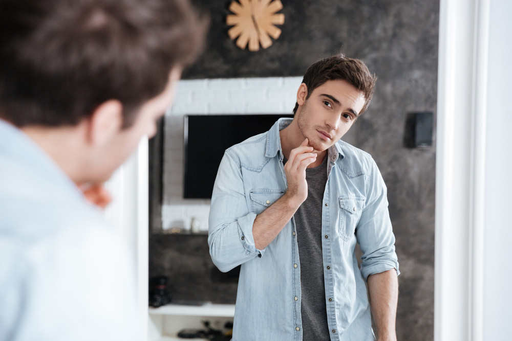 Handsome young man touching his face with hand and smiling while standing in front of the mirror