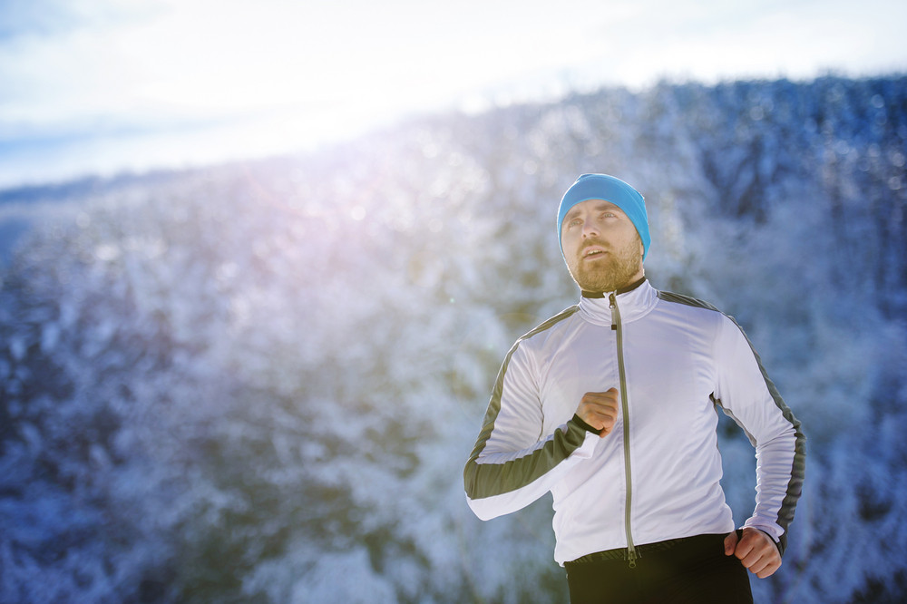 Handsome young runner in snowy winter nature