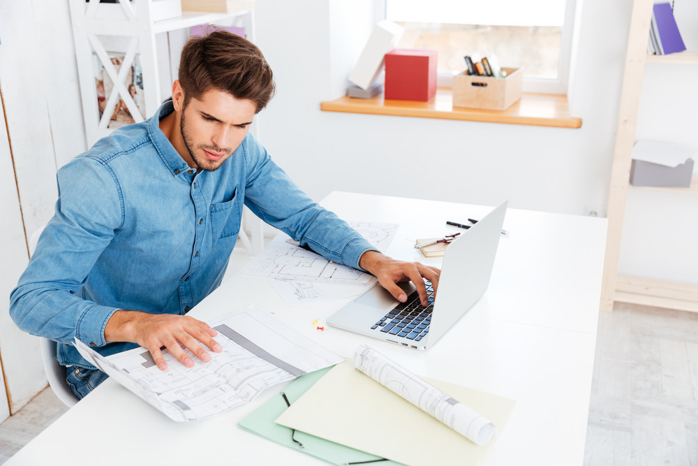 Handsome young smart businessman working with documents and computer in office
