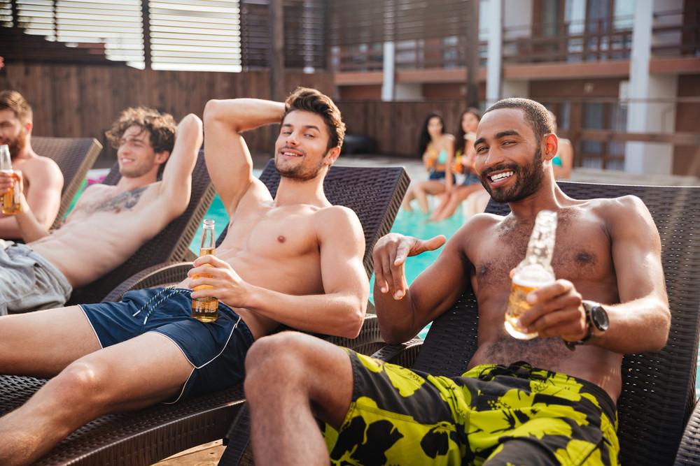 homens de sorriso novo considerável que tem o divertimento na piscina e beber cerveja