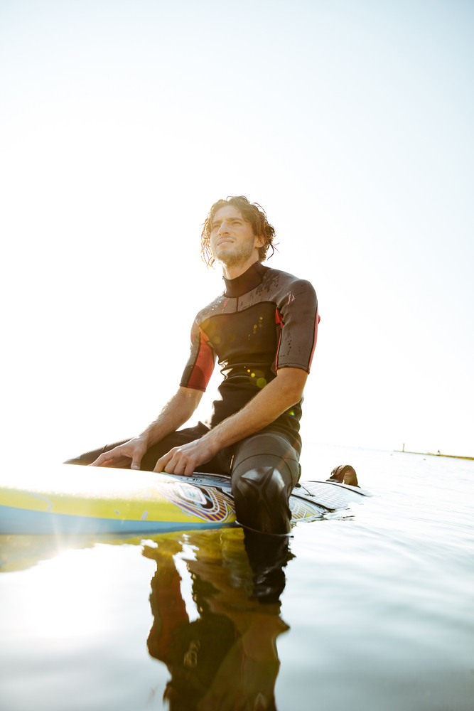 Handsome young surfer man in swimwear sitting on surf board in ocean