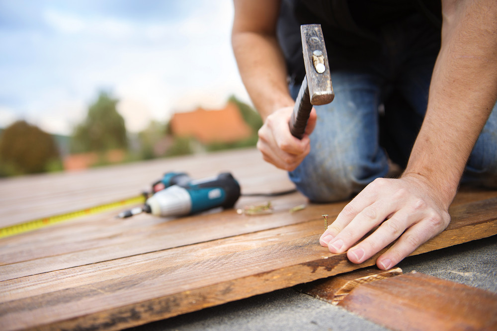 Handyman installing wooden flooring in patio, working with hammer