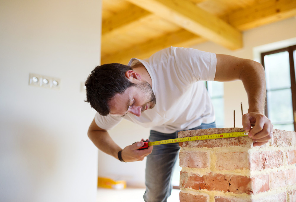 Handyman measuring unfinished room in new house