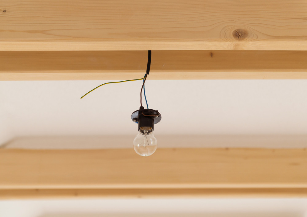 Hanging transparent glass bulb from unfinished construction.