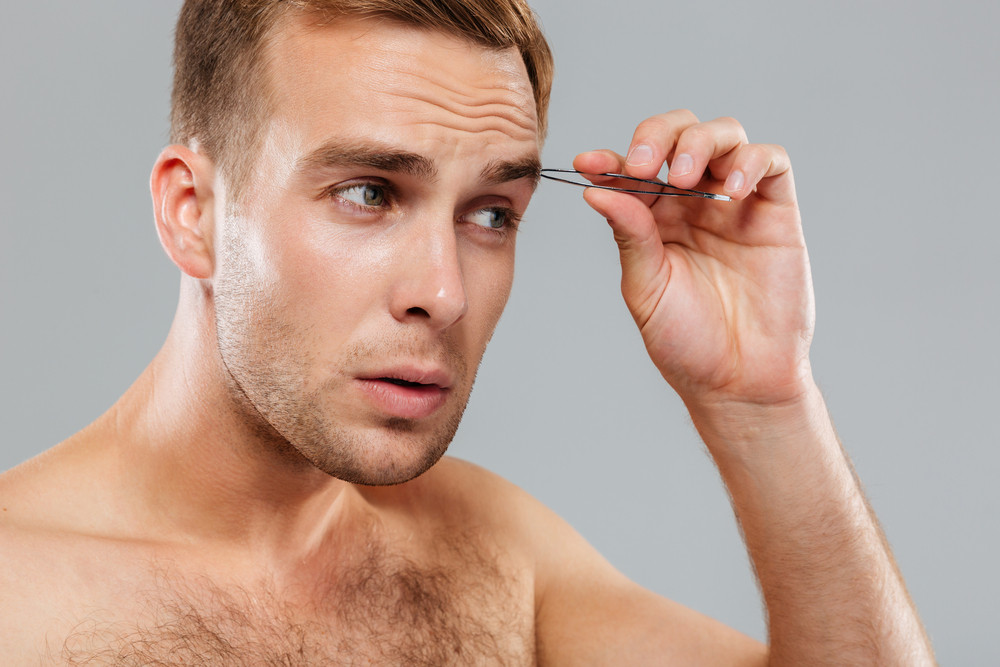 Hansome serious young man removing eyebrow hairs with tweezers
