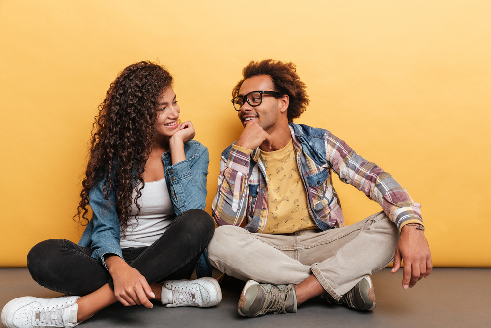 Happy african american young couple sitting and looking at each other over yellow background