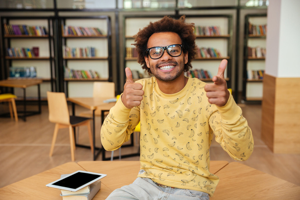 Happy african american young man in glasses showing thumbs up and pointing on you in library