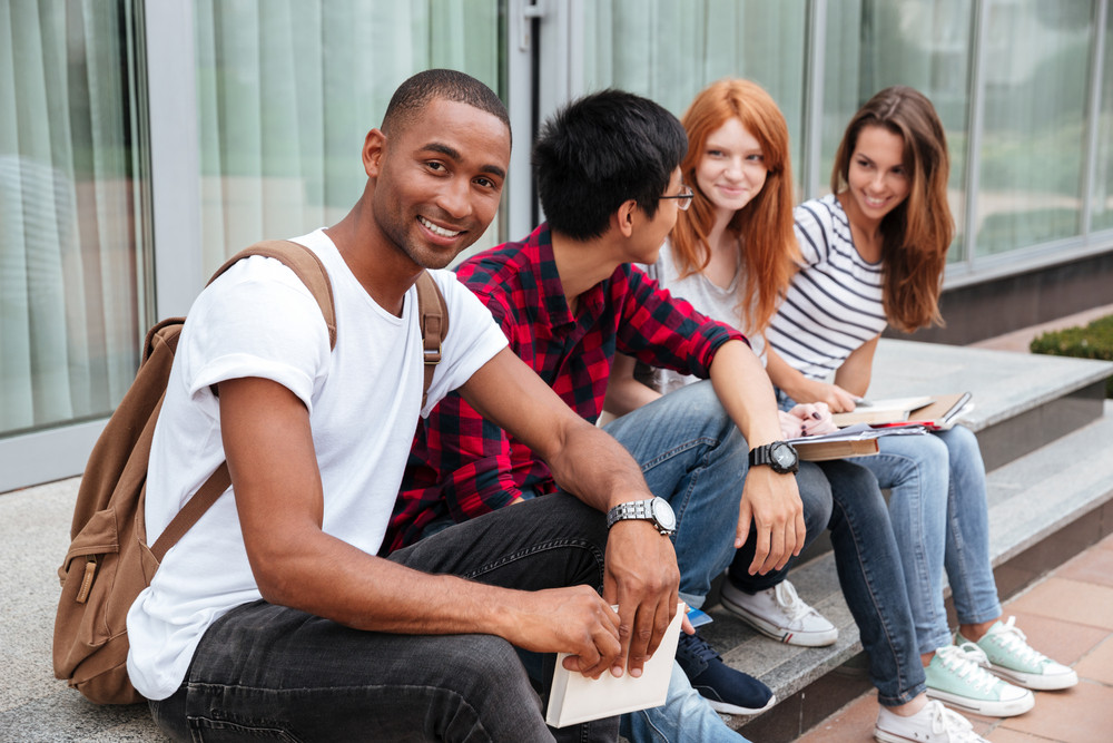 Happy african american young man student sitting with his frieds outdoors