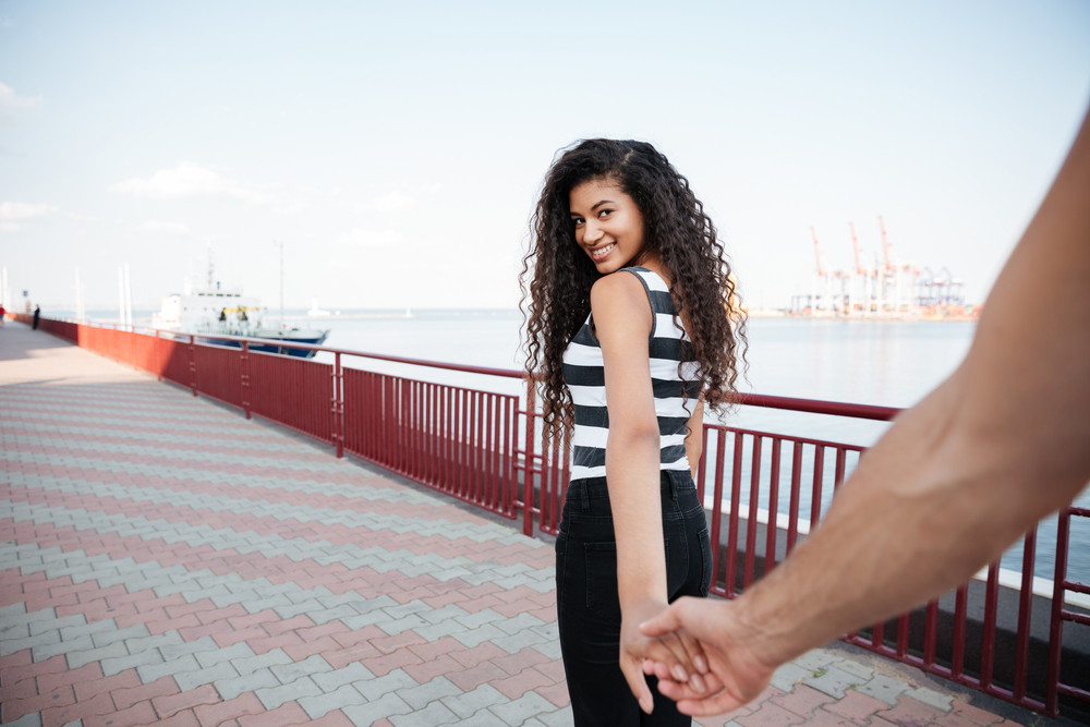 Happy african american young woman holding hads with her boyfriend and walking on promenade