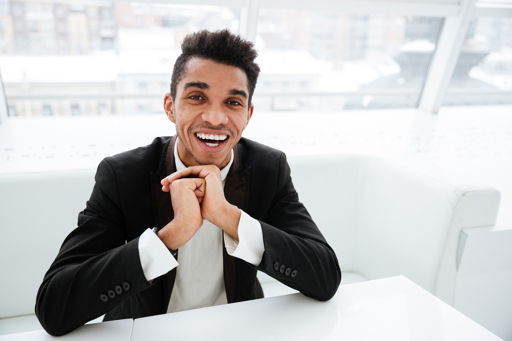 Happy african business man in black suit sitting at the table with hands near the face in office and looking at camera