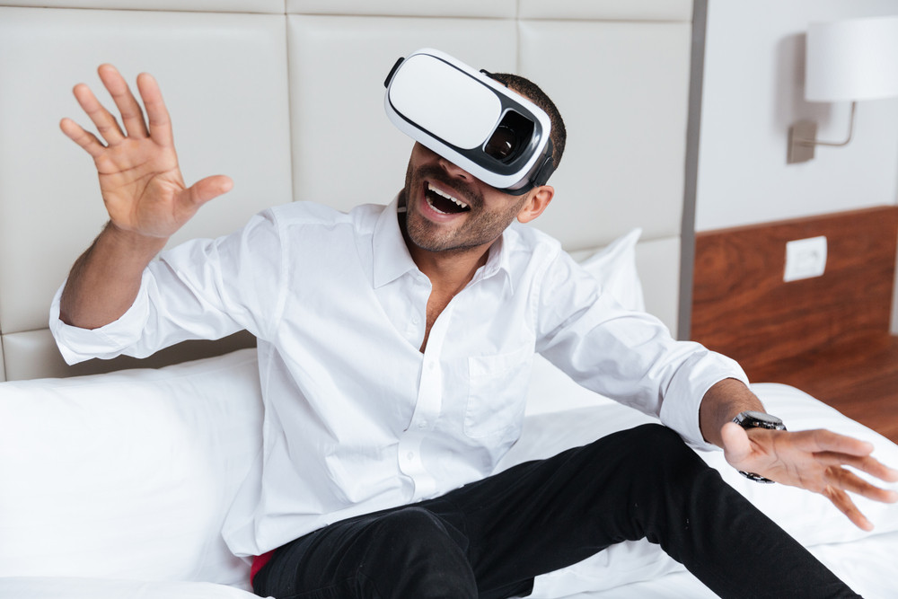 Happy African man in shirt with open mouth using virtual reality device sitting on bed in hotel