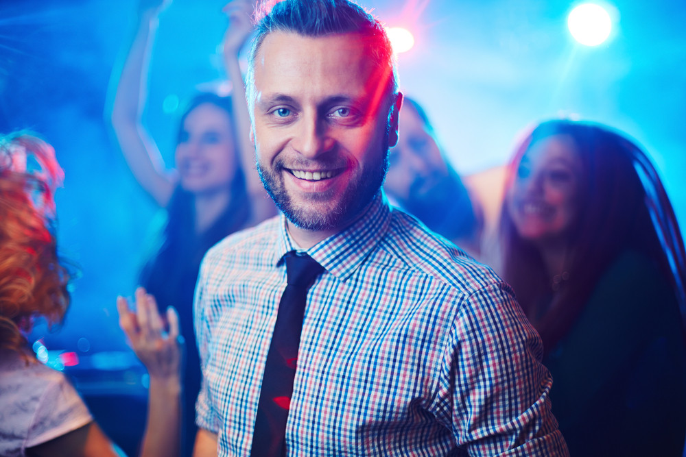 Happy and elegant man looking at camera at party